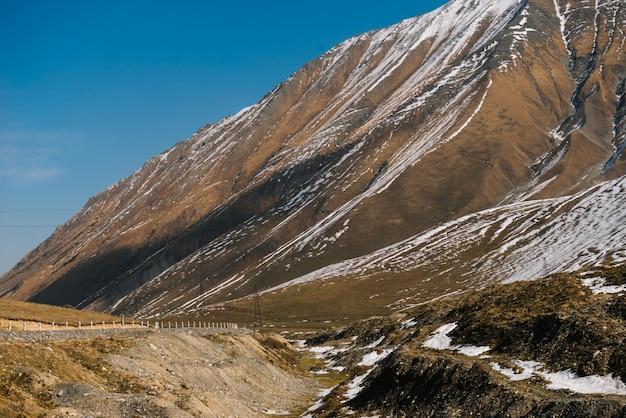 Magiczna czarująca przyroda, wysokie góry pokryte białym śniegiem pod błękitnym niebem