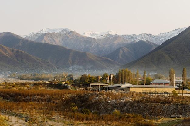 Magiczna czarująca przyroda, wysokie góry pokryte śniegiem, pola i drzewa