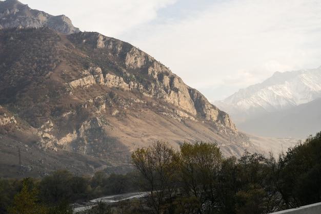 Magiczna czarująca przyroda, wysokie majestatyczne góry w promieniach porannego słońca