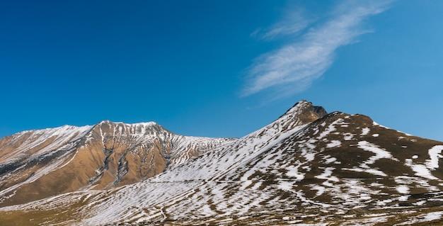 Magiczna czarująca przyroda, wysokie zbocza gór pokryte białym śniegiem, pod błękitnym niebem