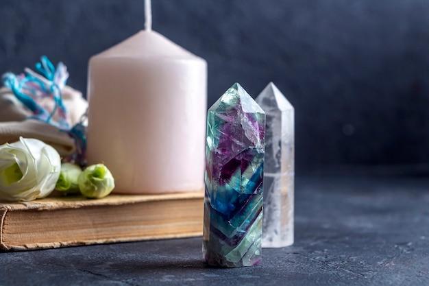 Magiczna kompozycja z różową świecą, kryształami, pogańską torebką i kwiatami.