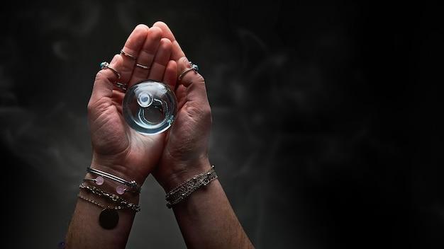 Magiczna kryształowa eliksirowa butelka z eliksirem do pisowni miłości, czarów i wróżbiarstwa w rękach czarodziejki na czarnym ciemnym tle. magiczna ilustracja i alchemia