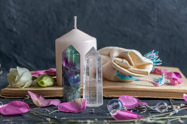 Magiczna martwa natura z fluorytowym kryształem kwarcu i różową świecą.