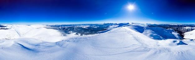 Magiczna panorama pięknego wzgórza w górach pokrytych śniegiem na stoku narciarskim w słoneczny dzień