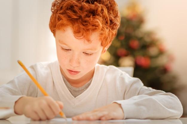 Magiczna pora roku. urocza ruda chłopiec siedzi przy stole i koncentrując się na kartce papieru podczas pisania listu do świętego mikołaja.