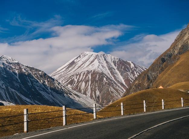 Magiczna przyroda i krajobraz, wysokie góry pokryte białym śniegiem, żółte pola i błękitne niebo