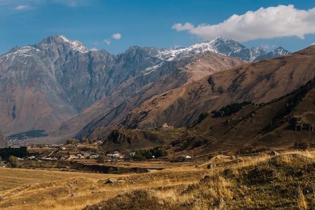 Magiczna przyroda, majestatyczne wysokie góry pokryte białym śniegiem, pod błękitnym niebem, żółte pola