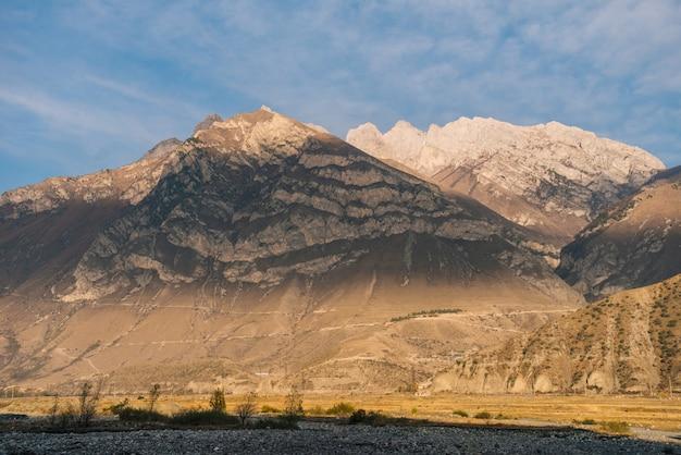 Magiczna przyroda, majestatyczne wysokie góry w słońcu pod błękitnym niebem