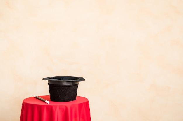 Magiczna różdżka i czarny cylinder na stole przed ścianą grunge z miejsca na kopię
