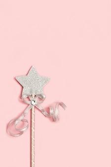 Magiczna różdżka jasna srebrna gwiazda z połyskiem na jasnoróżowej powierzchni