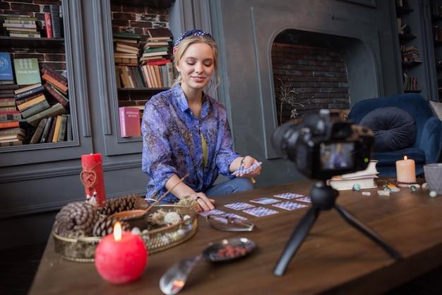 Magiczny blog. radosna szczęśliwa kobieta używająca kart tarota podczas nagrywania wideo na swoim blogu