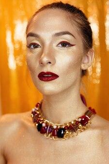 Magiczny portret dziewczyny w złocie. złoty makijaż, szczegół portret w studio strzał, kolor. model piękna dziewczyna z doskonały makijaż jasny, czerwone usta, biżuteria złota bordowy. sexy pani makijaż holiday party.