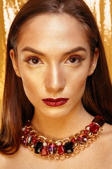 Magiczny portret dziewczyny w złocie. złoty makijaż, szczegół portret w studio strzał, kolor. model piękna dziewczyna z doskonały makijaż jasny, czerwone usta, złota bordowa biżuteria. sexy pani makijaż holiday party.