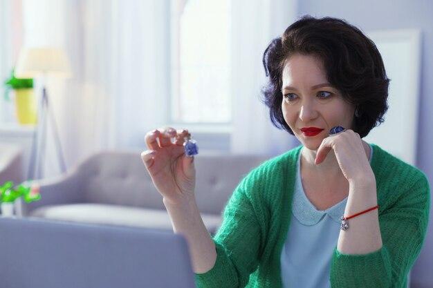 Magiczny przedmiot. miła ciemnowłosa kobieta trzymająca specjalną butelkę podczas praktykowania magii