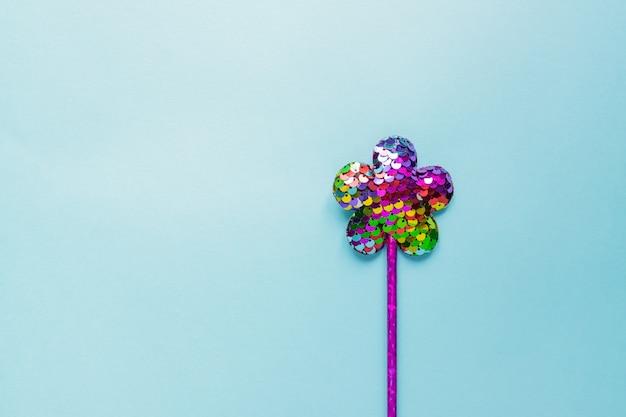 Magiczny sztyft z cekinami w kształcie kwiatu na pastelowym niebieskim tle. kreatywne mieszkanie leżało w minimalistycznym stylu
