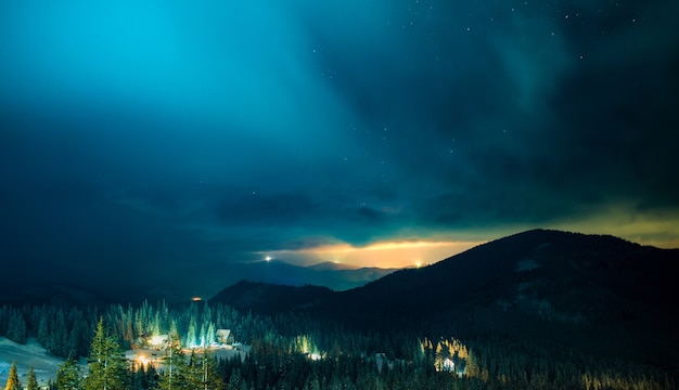 Magiczny widok na bazę narciarską w nocy z widokiem na zorzę polarną w pochmurną zimową noc. koncepcja nastroju bożego narodzenia i nowego roku. miejsce na tekst