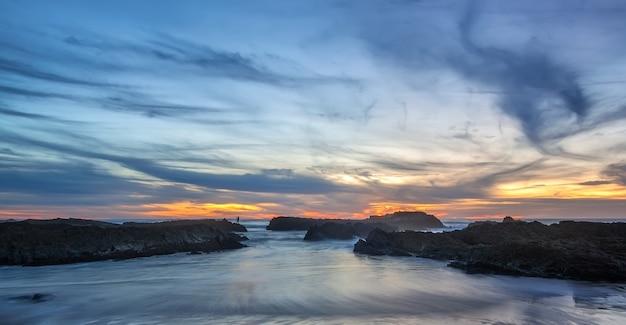 Magiczny zachód słońca na portugalskim wybrzeżu z postacią kobiety w tle.