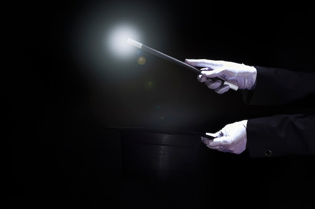 Magik wykonuje sztuczkę z magiczną różdżką nad czarnym odgórnym kapeluszem przeciw czarnemu tłu