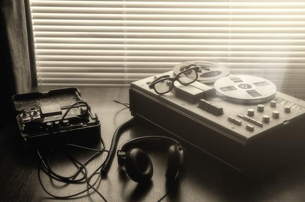 Magnetofon szpulowy do podsłuchu. nieopodal leży polowy aparat telefoniczny zsrr. rozmowy szpiegowskie kgb.
