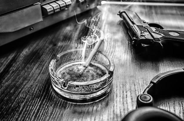 Magnetofon szpulowy do podsłuchu. rozmowy szpiegowskie kgb. czarny pistolet w pobliżu. popielniczka z papierosem.