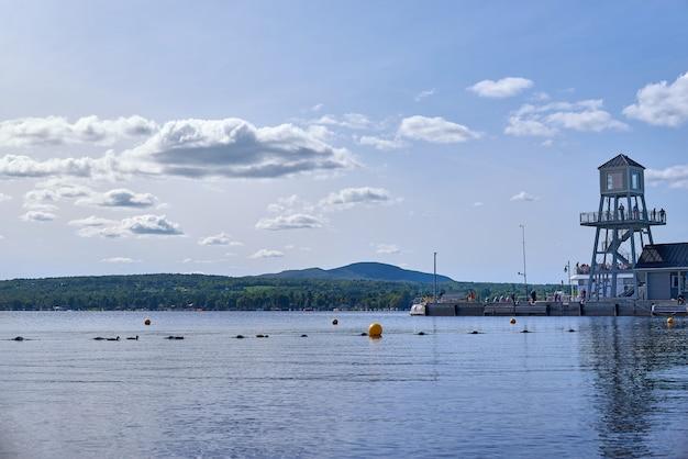 Magog, quebec, kanada - 8 września 2018 r .: nabrzeże i wieża obserwacyjna wieczorem nad jeziorem memphremagog w magog