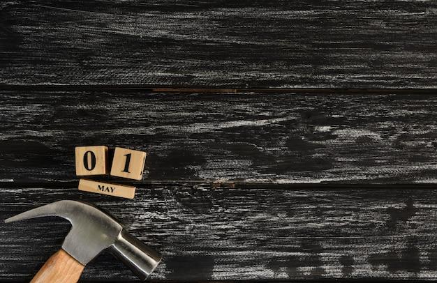 Maj 1 tekst drewniany blokowy kalendarz i młot na czarnym drewnianym tle.