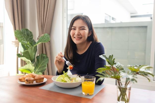 Mając koncepcję posiłku ładna kobieta mieszająca sos sałatkowy zero kalorii z zieloną sałatą