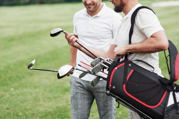 Mając konwergencję i uśmiech. przycięte zdjęcie dwóch przyjaciół na boisku sportowym ze sprzętem do golfa.