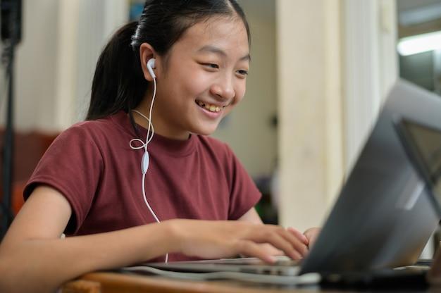 Mając lekcję online. azjatyckie dzieci samodzielnie uczą się z e-learningiem w domu. koncepcja edukacji online i samokształcenia oraz nauczania w domu.