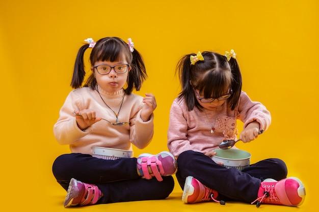 Mając lekkie śniadanie. ciemnowłose niezwykłe dzieci z nieprawidłowościami chromosomowymi jedzą śniadanie siedząc razem