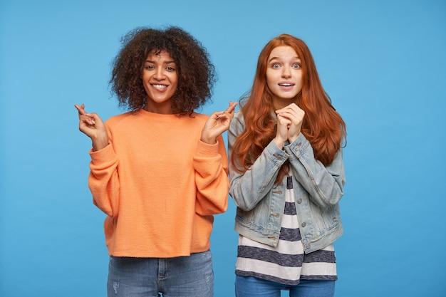 Mając nadzieję, że atrakcyjne młode kobiety wyglądają niepokojąco i trzymają ręce podniesione, odizolowane na niebieskiej ścianie w codziennym noszeniu