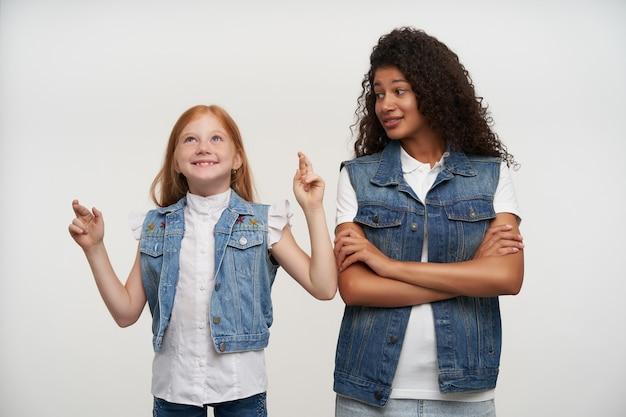 Mając nadzieję, że wesołe dziecko płci żeńskiej z lśniącymi włosami patrzy w górę i trzyma kciuki na szczęście, pozuje na biało z młodą brunetką, ciemnoskórą kobietą, patrzącą na nią z miłością