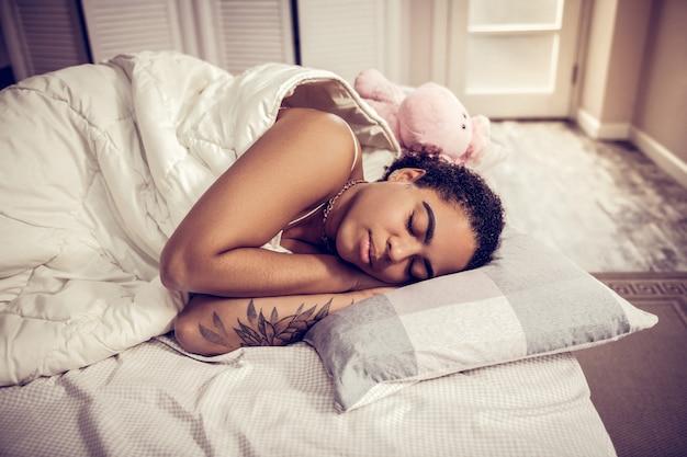 Mając przyjemne sny. ładna ciemnowłosa pani spokojnie śpiąca przykryta miękkim kocem i mająca w pobliżu pluszową zabawkę