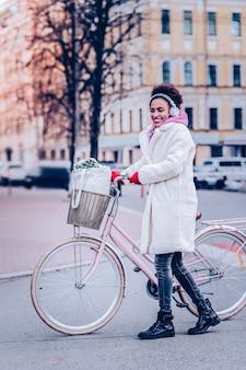 Mając spotkanie. zadowolona dziewczyna trzyma kierownicę stojąc obok swojego roweru