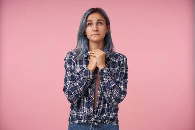 Mająca nadzieję, młoda urocza kobieta z naturalnym makijażem składająca dłonie w geście modlitwy, patrząc rozpaczliwie w górę, odizolowana na różowo w kraciastej koszuli
