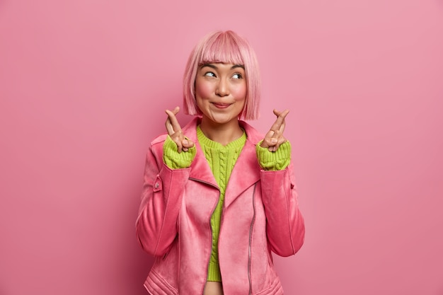 Mająca nadzieję, różowowłosa azjatka trzymająca kciuki na szczęście wierzy w coś miłego, skupiona na boku i starannie ubrana w stylową kurtkę.
