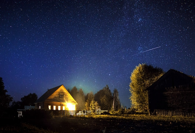Majestatyczna droga mleczna i spadająca gwiazda nad wiejskim domem w lecie. gwiaździste nocne niebo.