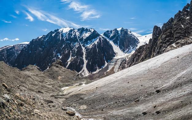 Majestatyczna polodowcowa dolina górska z wąwozem na tle wysokich, ośnieżonych gór. panoramiczny widok na lodowiec, wysoko w górach, pokryty śniegiem i lodem. zimowy krajobraz ałtaju.