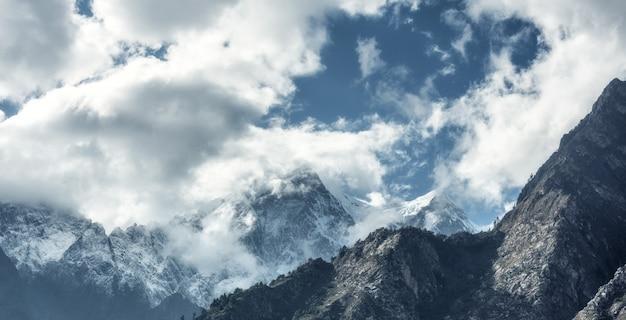 Majestatyczna scena z górami z śnieżnymi szczytami w chmurach w nepal
