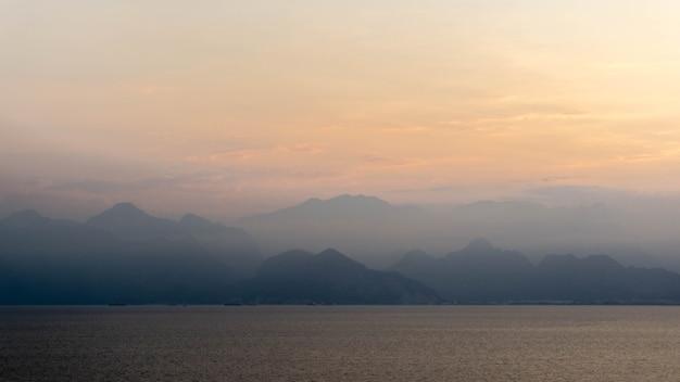 Majestatyczne góry pokryte chmurami i mgłą, letni dzień