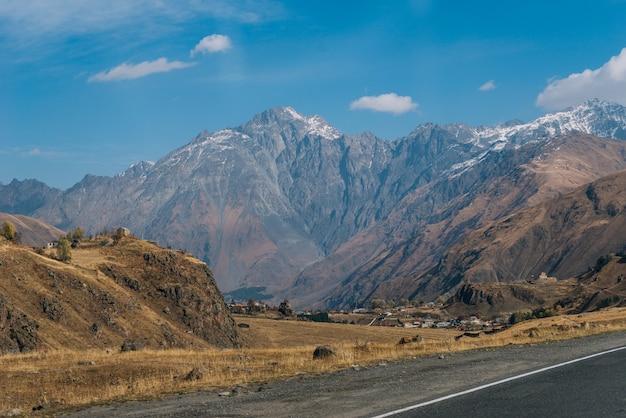 Majestatyczne wysokie góry pod błękitnym niebem, żółte pola i wzgórza