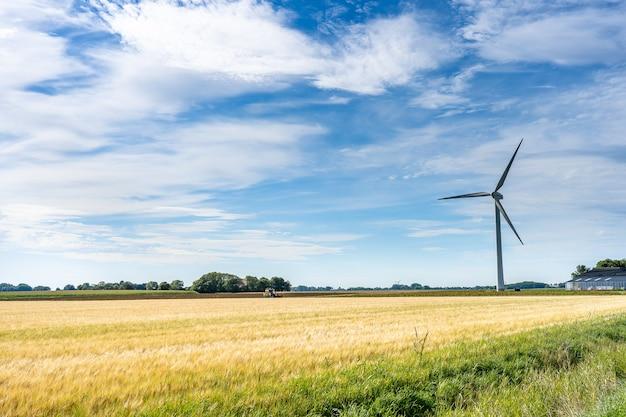 Majestatyczny widok na krajobraz ziemi z wiatrakiem do wytwarzania energii elektrycznej pod zachmurzonym niebem