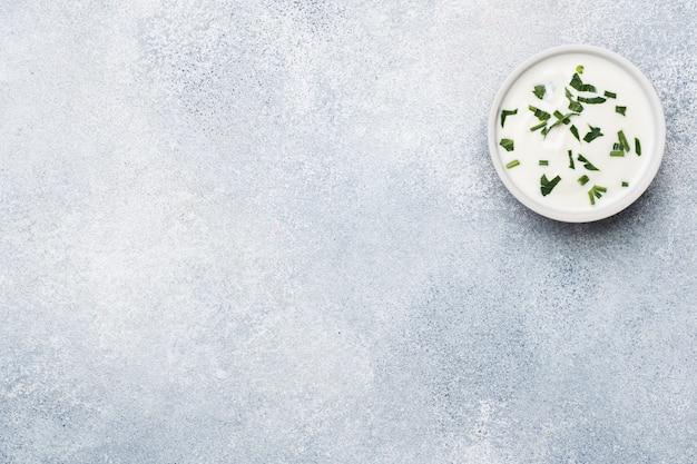 Majonezowe warzywa w talerzach na szarym betonowym stole z miejsca na kopię.