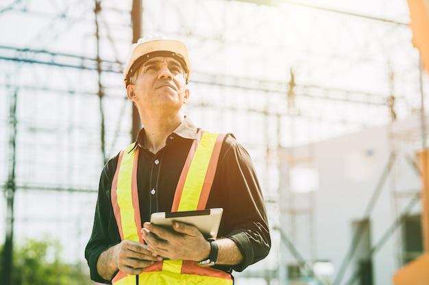 Majster budowniczy inżynier pracownik patrząc na duży budynek budowy słoneczny dzień ciężkiej pracy.