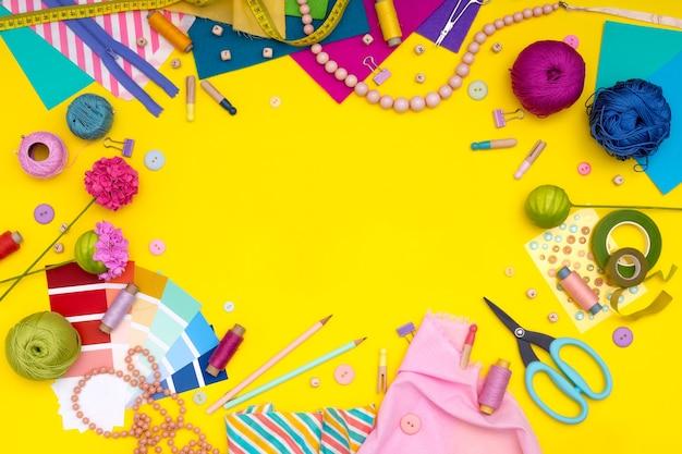 Majsterkowanie. wielokolorowe materiały rzemieślnicze i narzędzie na żółtym tle. hobby damskie - szycie, hafty, filcowe rzemiosło, scrapbooking. skopiuj miejsce.