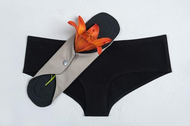 Majtki i bambusowy węgiel zmywalny podpaski higieniczne z czerwonym kwiatem na szarym tle. zdrowa damska podpaska higieniczna, wielorazowa podpaska menstruacyjna. opieka zdrowotna, zero odpadów, ekologiczna koncepcja.
