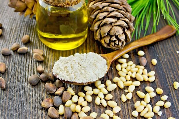 Mąka cedrowa w drewnianej łyżce, orzechy cedrowe i dwie szyszki, olej cedrowy w szklanym słoju, gałązka cedrowa z zielonymi igłami na tle desek