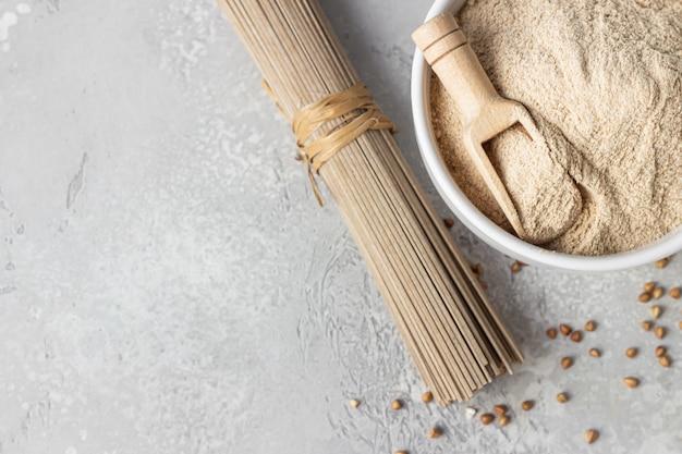 Mąka gryczana w misce, mała drewniana miarka z mąką i makaronem soba