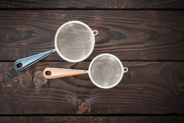 Mąka i sitko na starym drewnianym stole