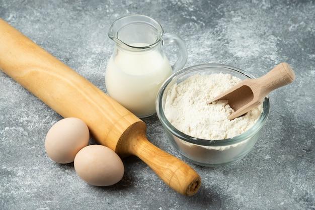 Mąka, jajka, mleko i wałek do ciasta na marmurowej powierzchni.